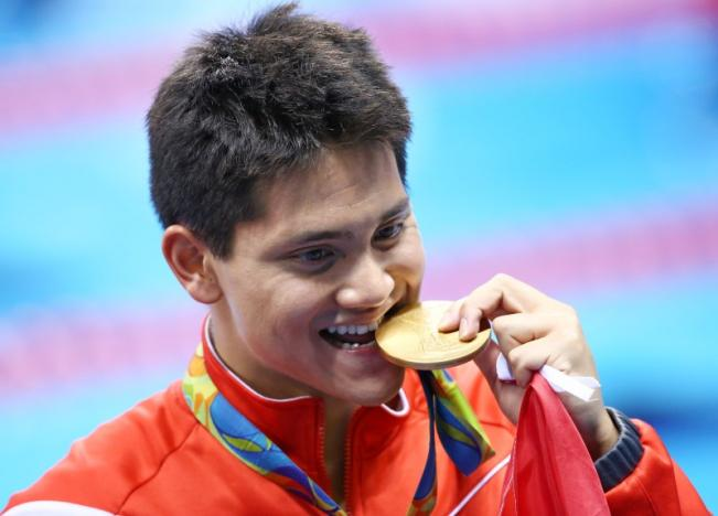 Joseph Schooling of Singapore poses with his gold medal.    REUTERS/Marcos Brindicci