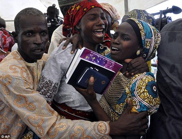 A father and mother were overcome with emotion when they are reunited with their daughter, one of 21 freed after being kidnapped by Boko Haram, at the weekend