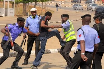 Photo Of A Nigerian Man Wrestling With 5 Armed Police Officers Goes Viral