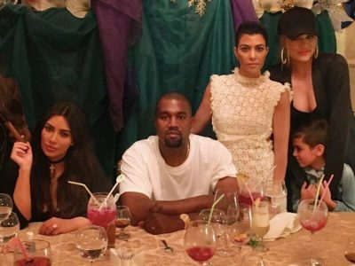 Kanye West flanked by the Kardashian sisters